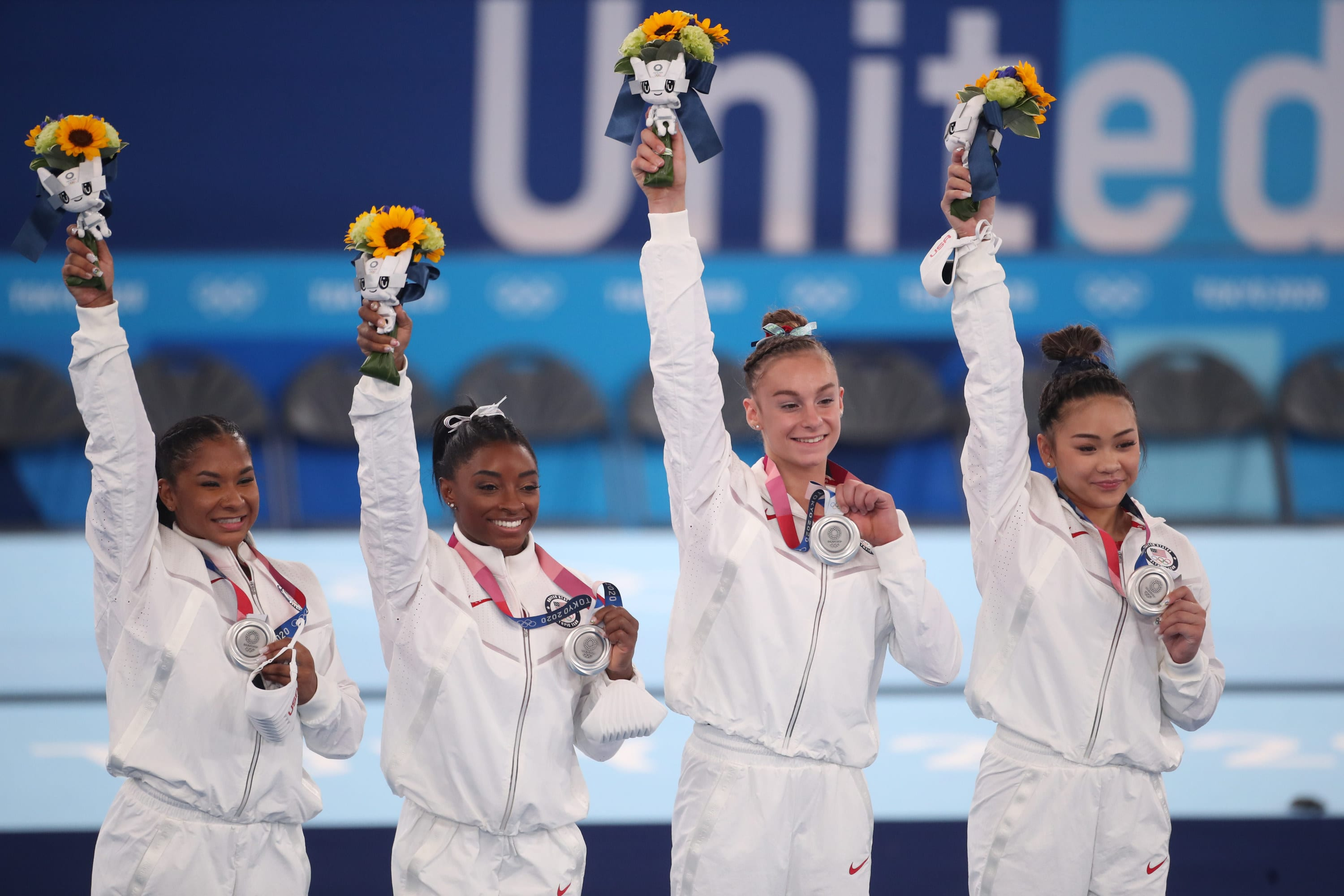 The U.S. Women's Gymnastics team saluting the crowd and posing with their medals