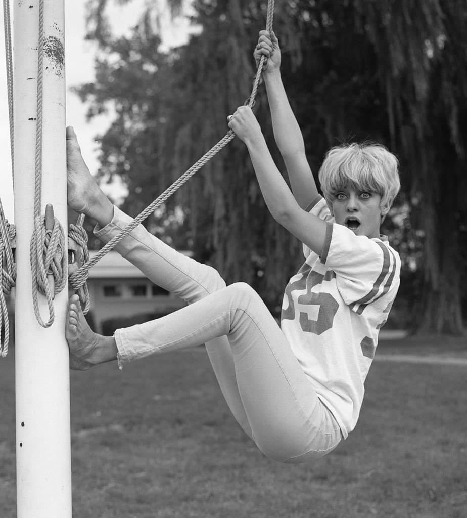 goldie se pendurando em uma corda e fazendo uma cara engraçada