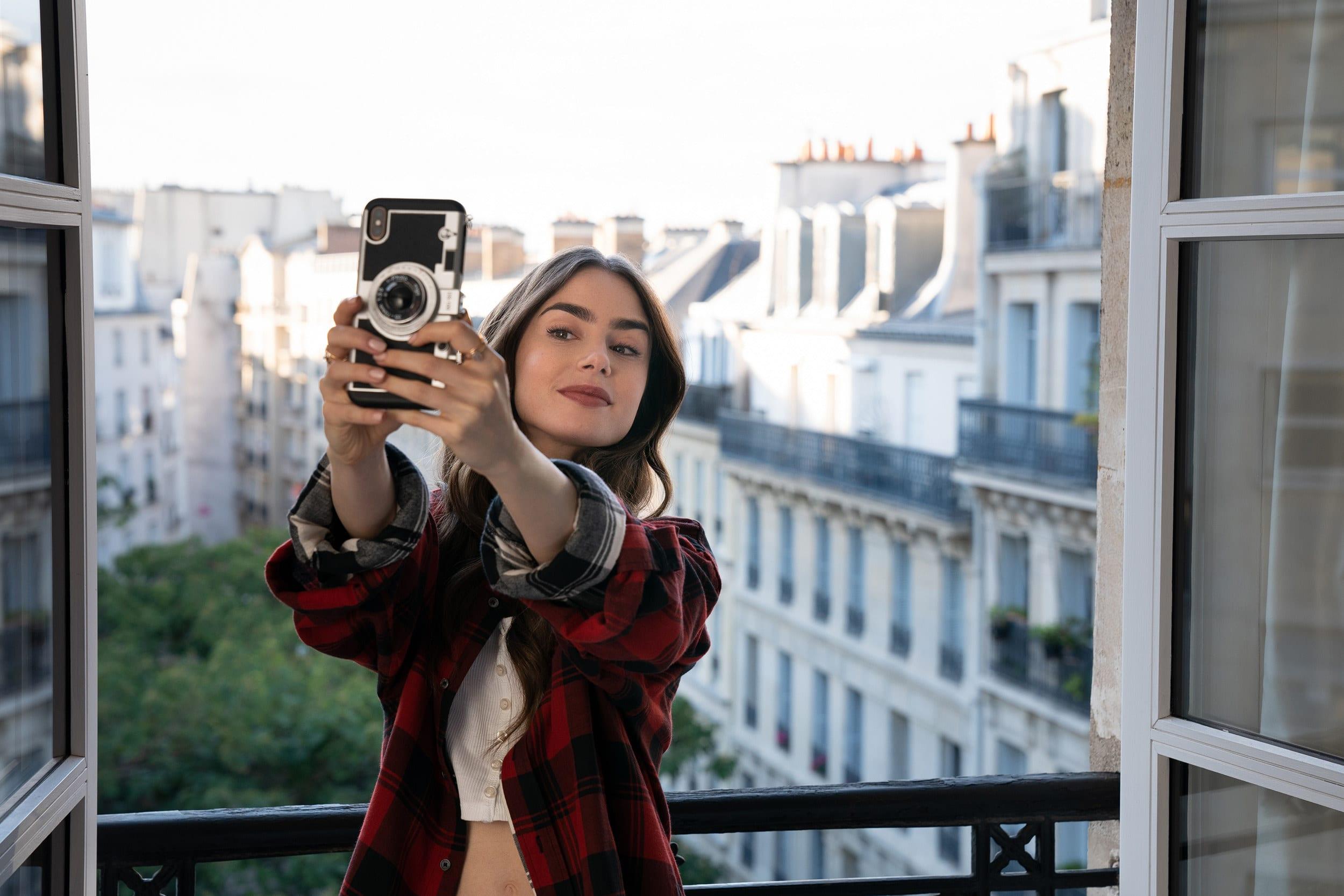 """Cena de """"Emily em Paris"""", Lilly Collins tirando uma selfie numa janela."""