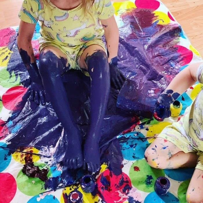 Duas crianças sentadas num plástico, elas estão inteiras sujas de tinta.