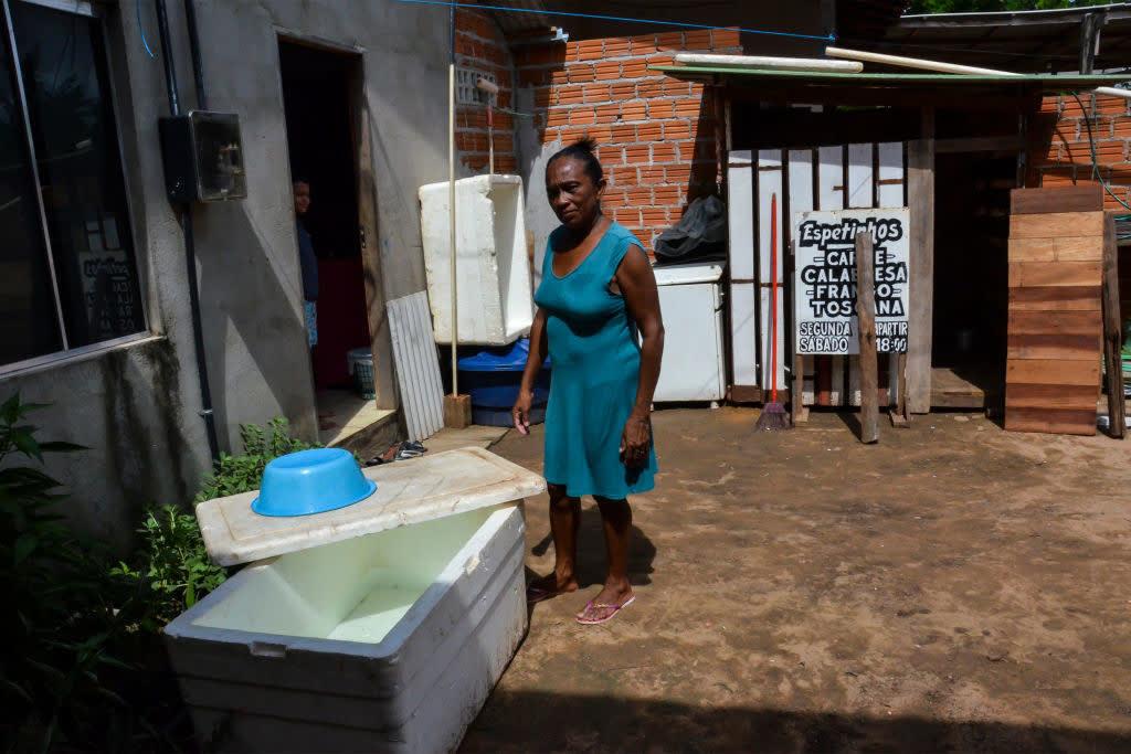Uma senhora mostra a caixa de isopor onde ela está armazenando água.