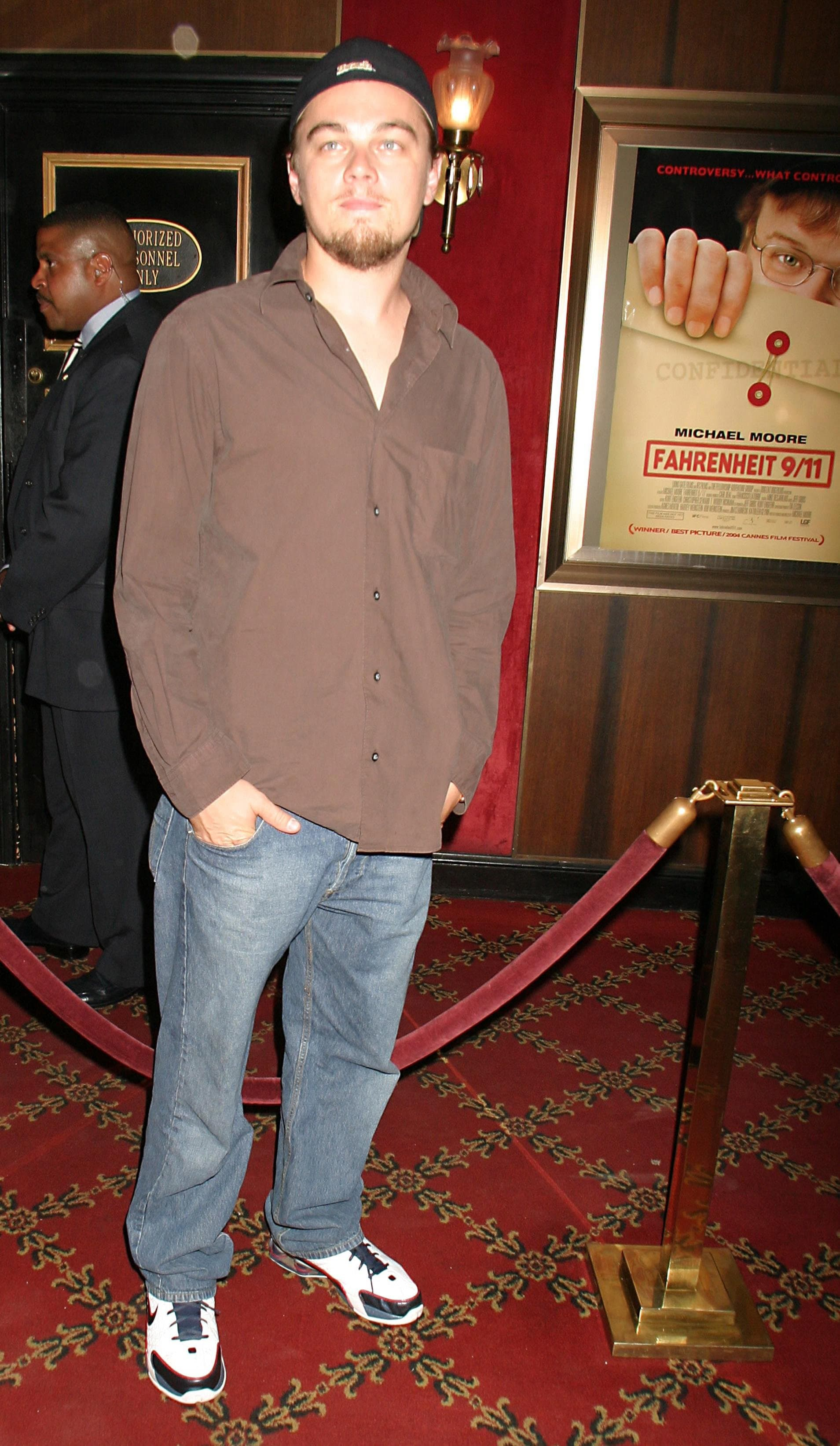 Leo is wearing a backwards baseball hat, an oversized brown button-down that is untucked, a pair of baggy light wash jeans, and Nike sneakers.