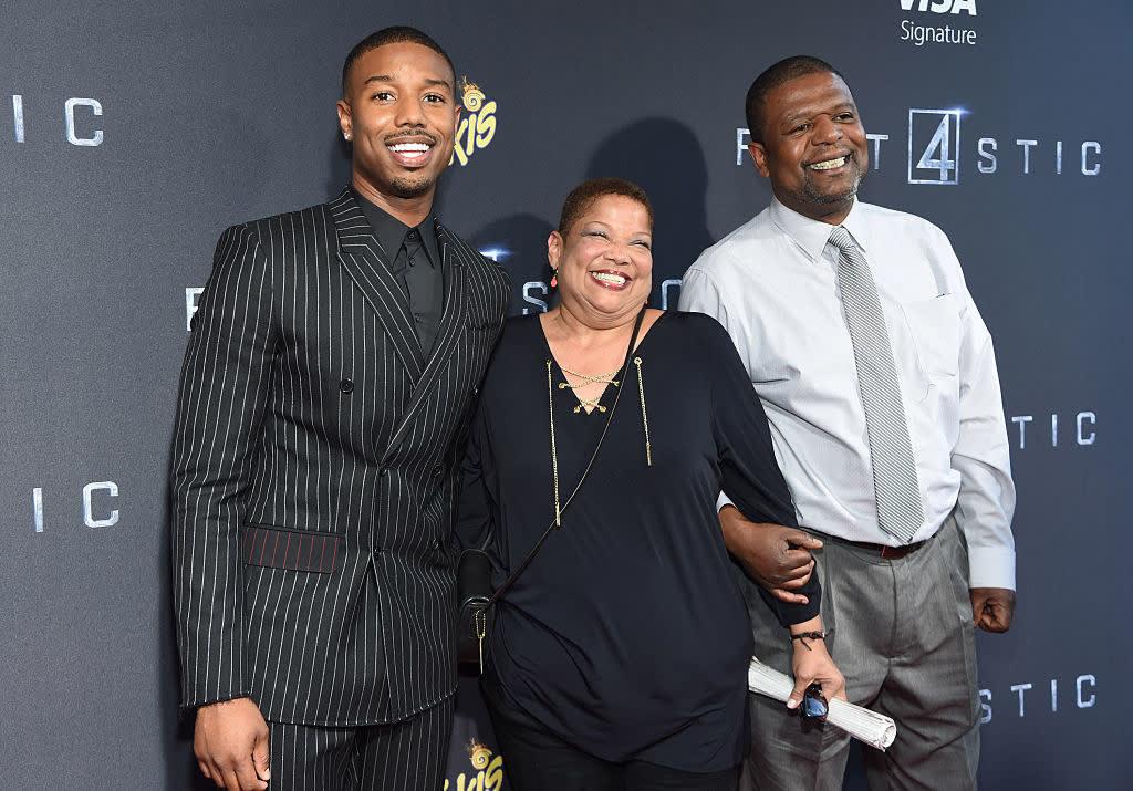 Michael B. Jordan em um tapete vermelho com sua mãe e seu pai.