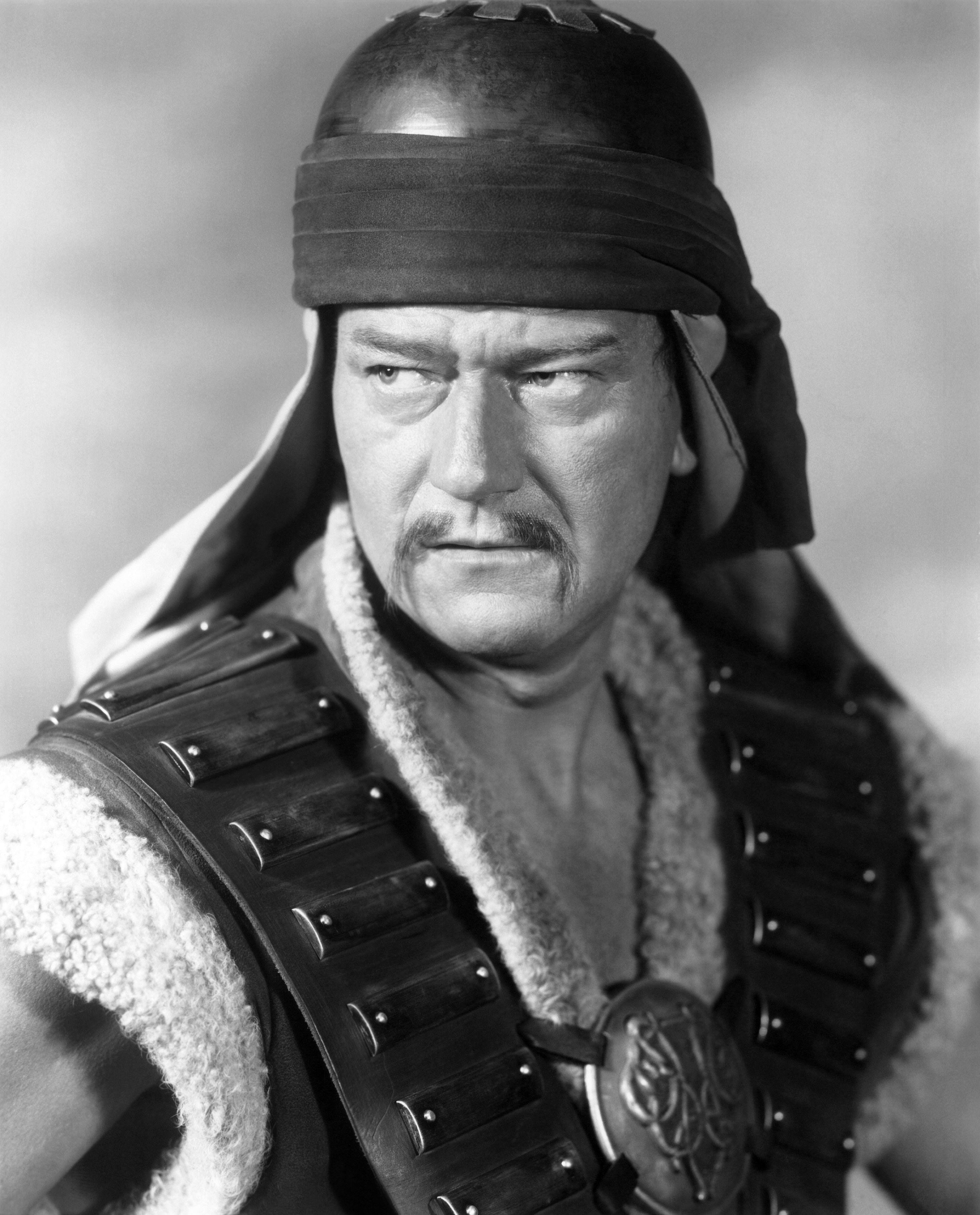 John Wayne is dressed up as Genghis Khan in a helmet and vest