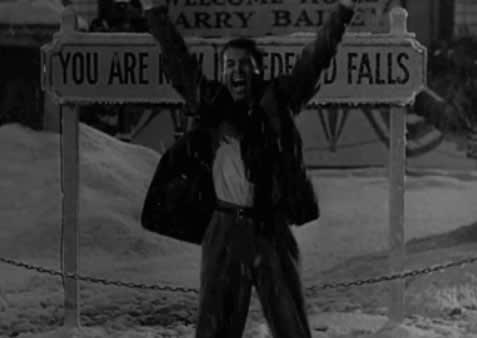 """George Bailey na neve na frente de uma placa em """"A Felicidade Não Se Compra"""""""