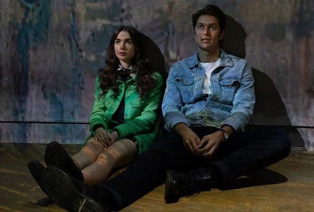 """Cena da série """"Emily em Paris"""". Lilly Collins como Emily e Lucas Bravo como Gabriel sentados."""