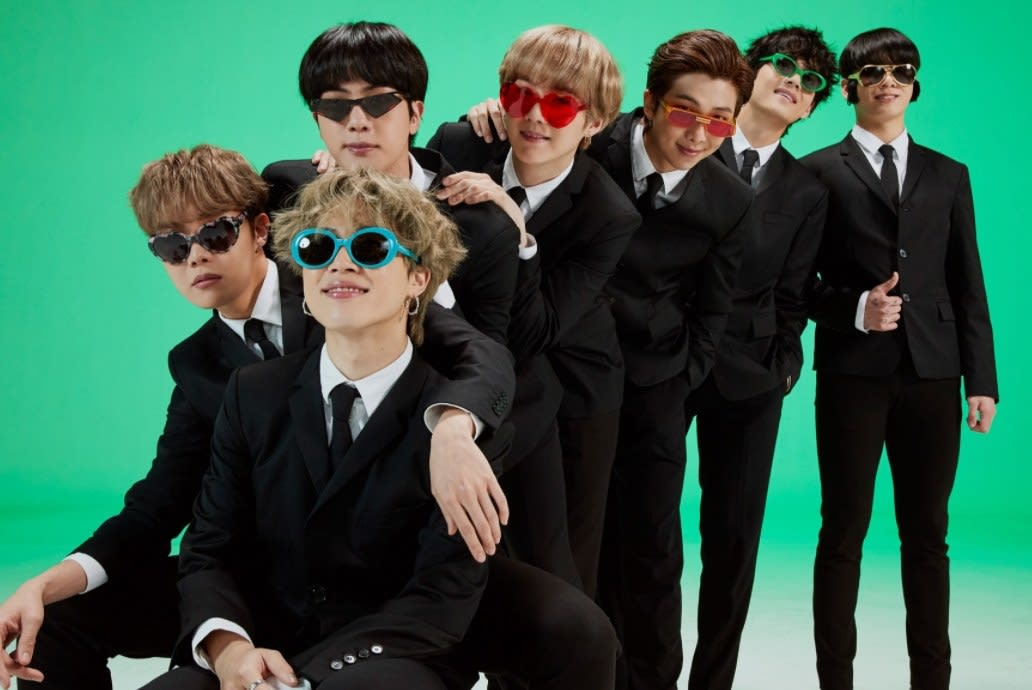 BTS wear suits and novelty sunglasses while lined up in a green studio
