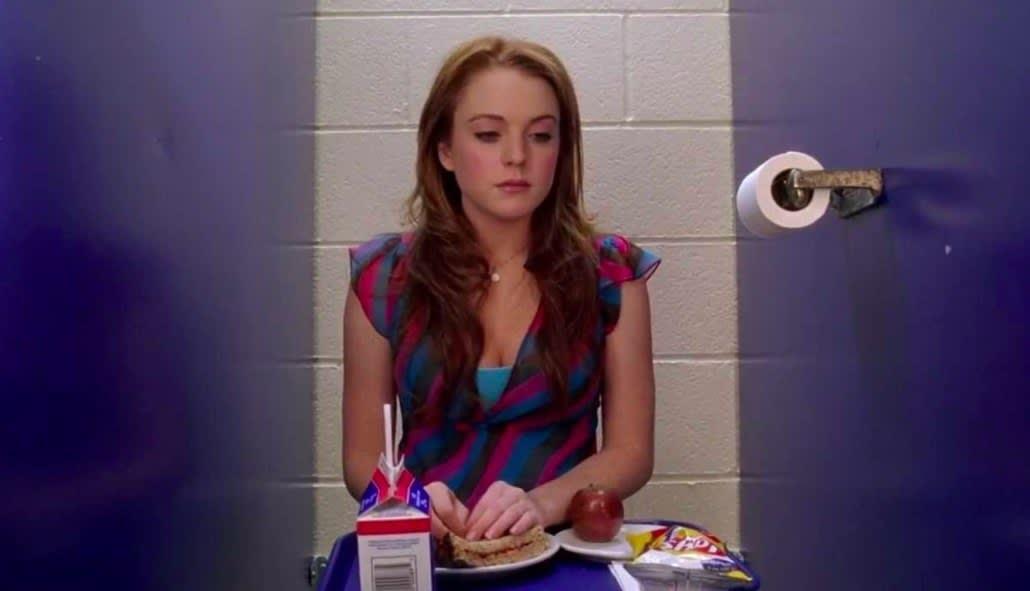"""Cady sentada com a bandeja no colo em """"Meninas Malvadas"""""""