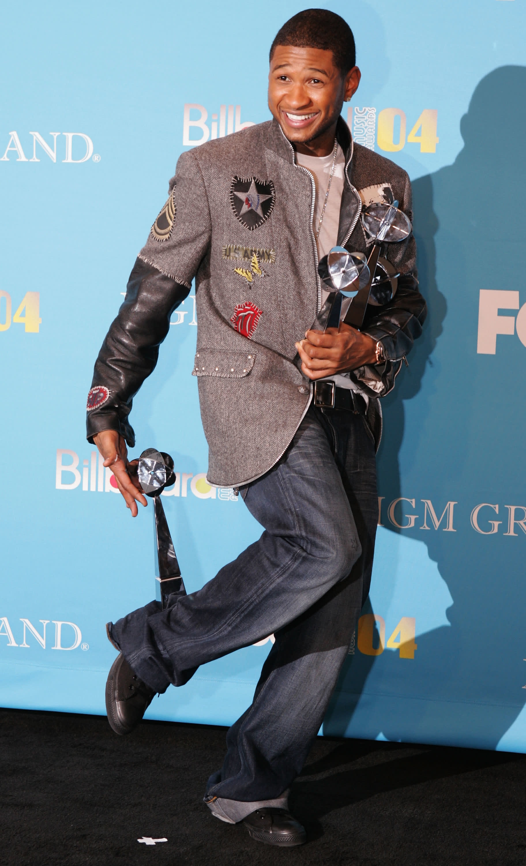 Usher wears a long patchwork jacket with leather sleeves and baggy jeans.