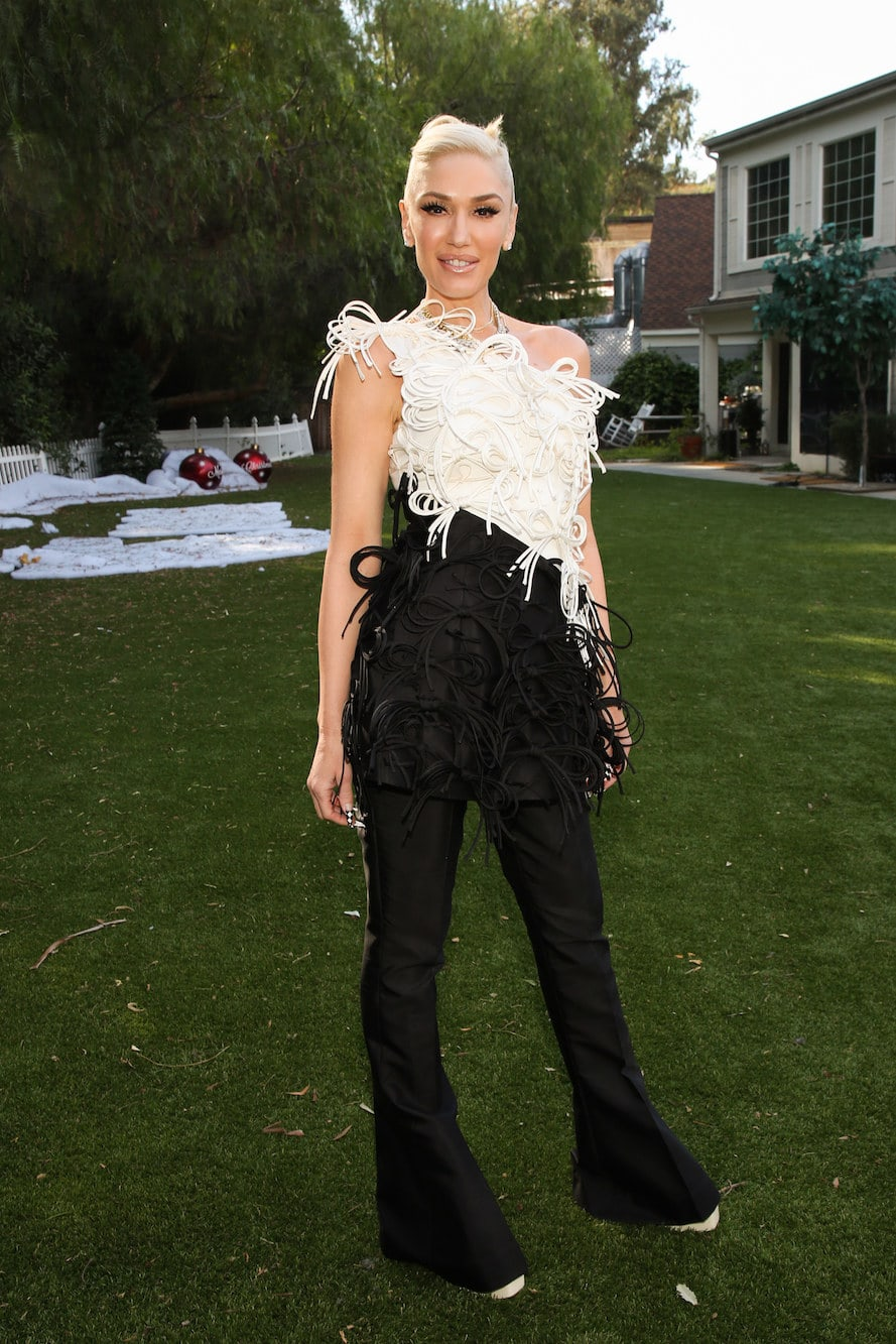 Gwen wears a one shoulder two toned top with tiny shoelace-like bows all over. She also wears bell bottom pants.