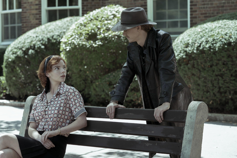 Beth sentada num banco e Benny em pé ao lado dela