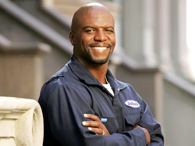 """O personagem Julius Rock, pai do Chris, da série """"Todo mundo odeia o Chris"""" sorrindo de braços cruzados"""