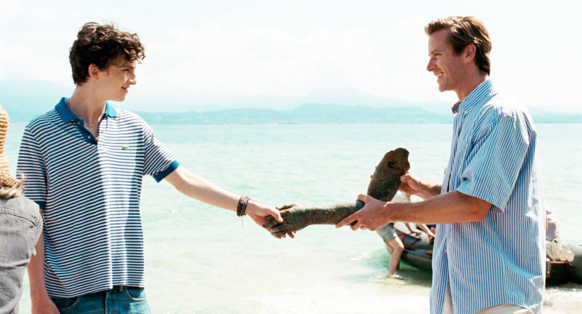 Timothée Chalamet and Armie Hammer look at each other as they hold a piece of driftwood