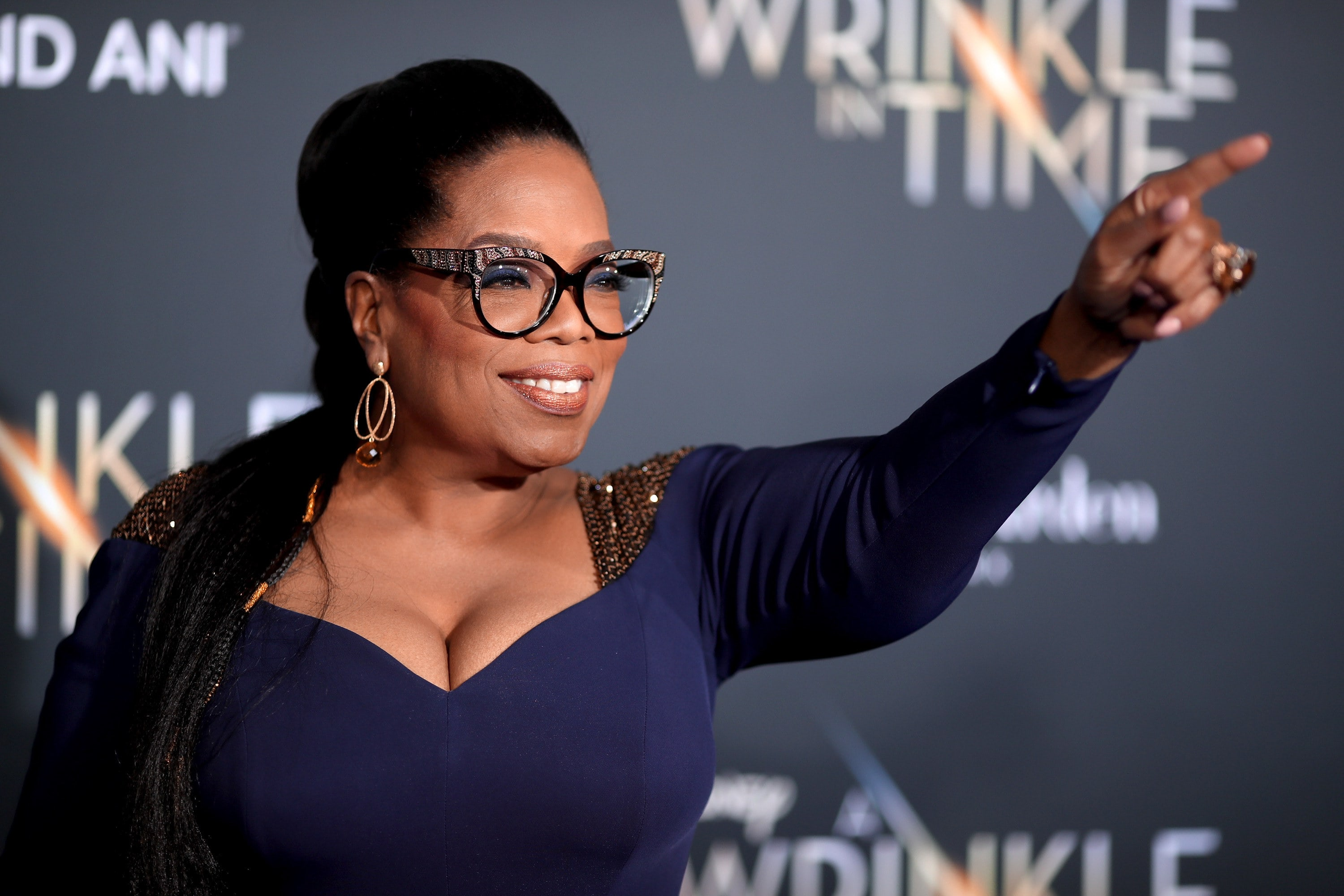 Oprah points in the distance at a red carpet event