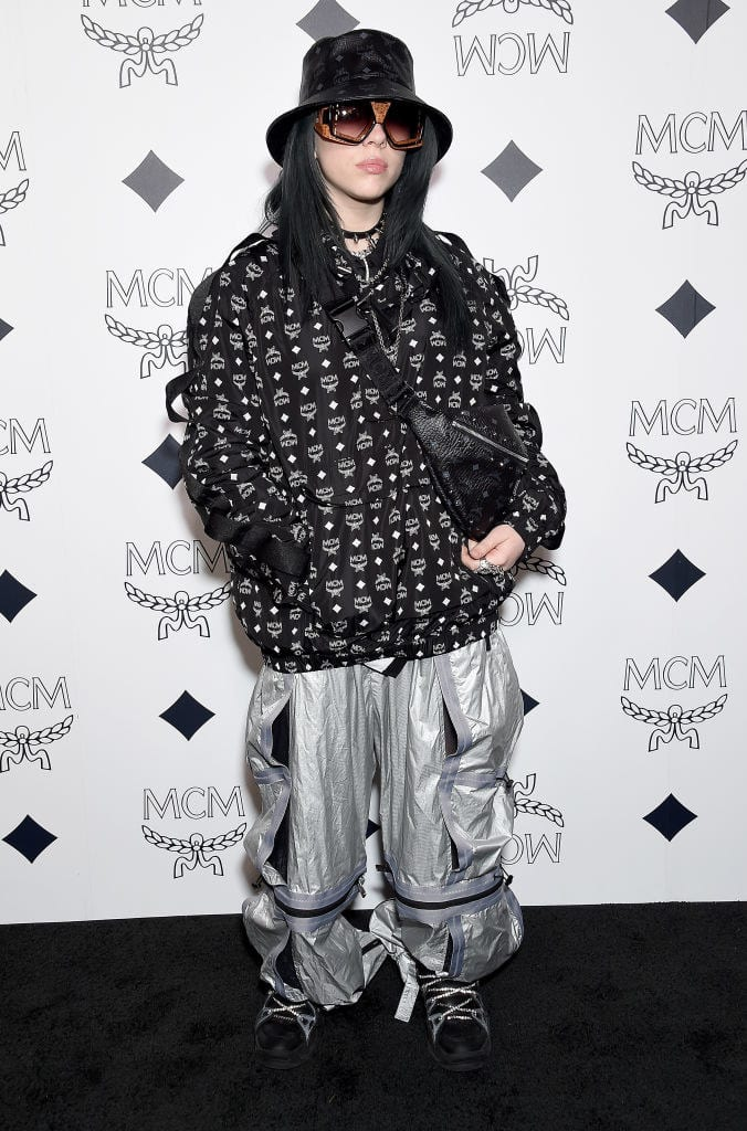 Billie no tapete com calças refletivas e casaco preto