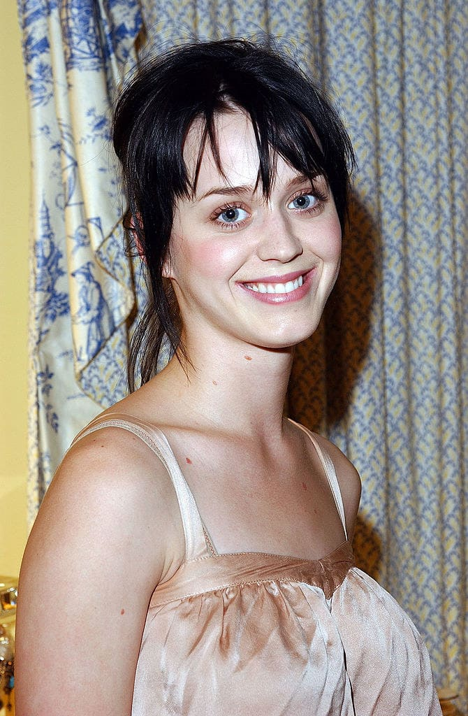 A fresh-faced, smiling Katy in a thin-strapped top