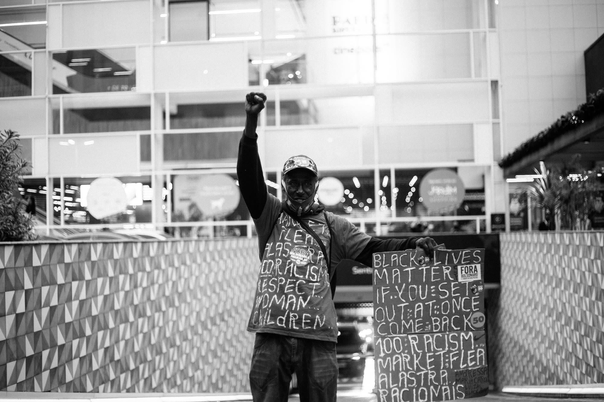 Homem com punho erguido usa moletom com palavras diversas: black lives matter, if you set out at once come back, 100 rascismo, market flea, alastra, racionais, respect woman & children.