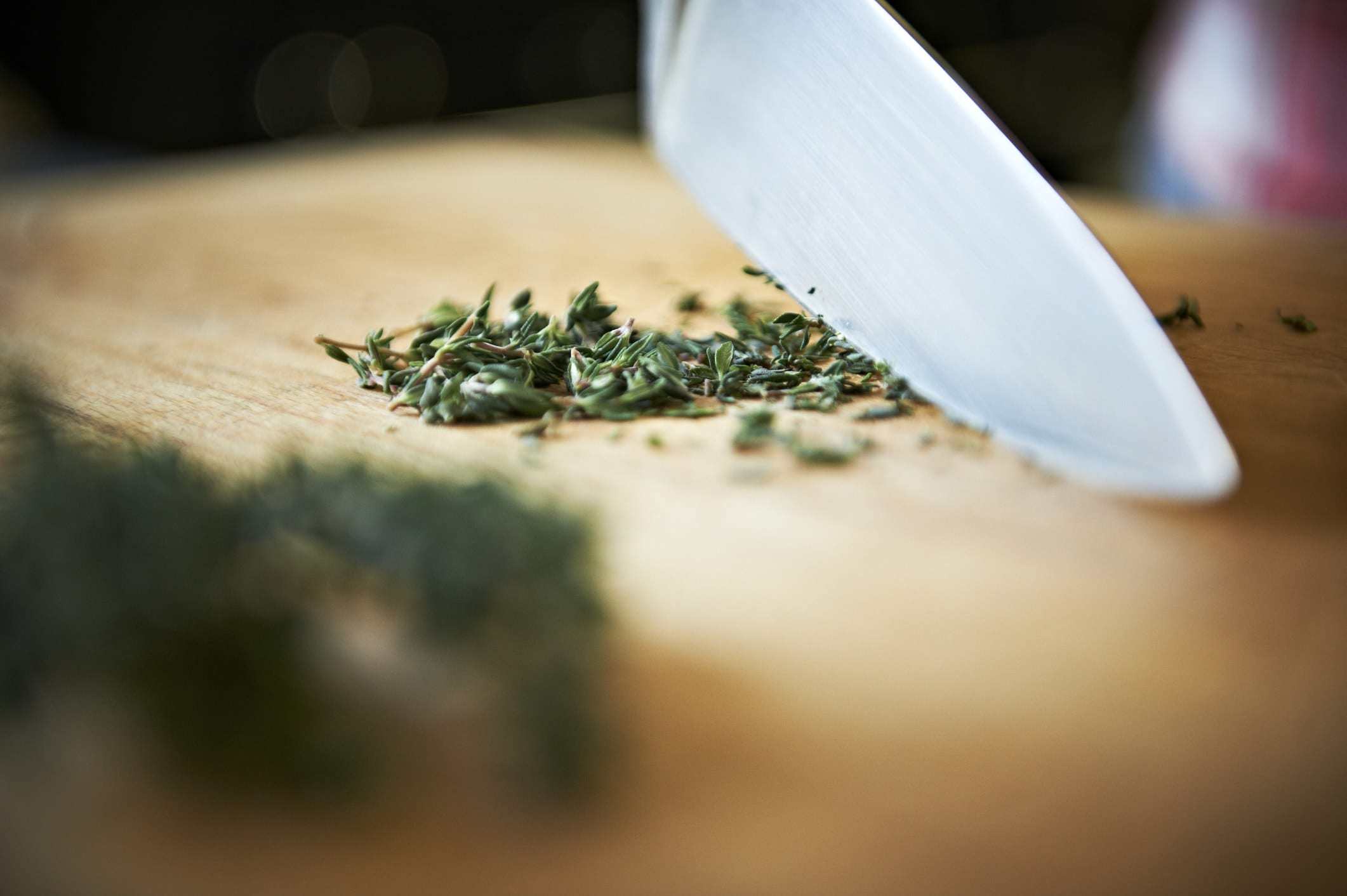 Thinly slicing herbs with a sharp knife.
