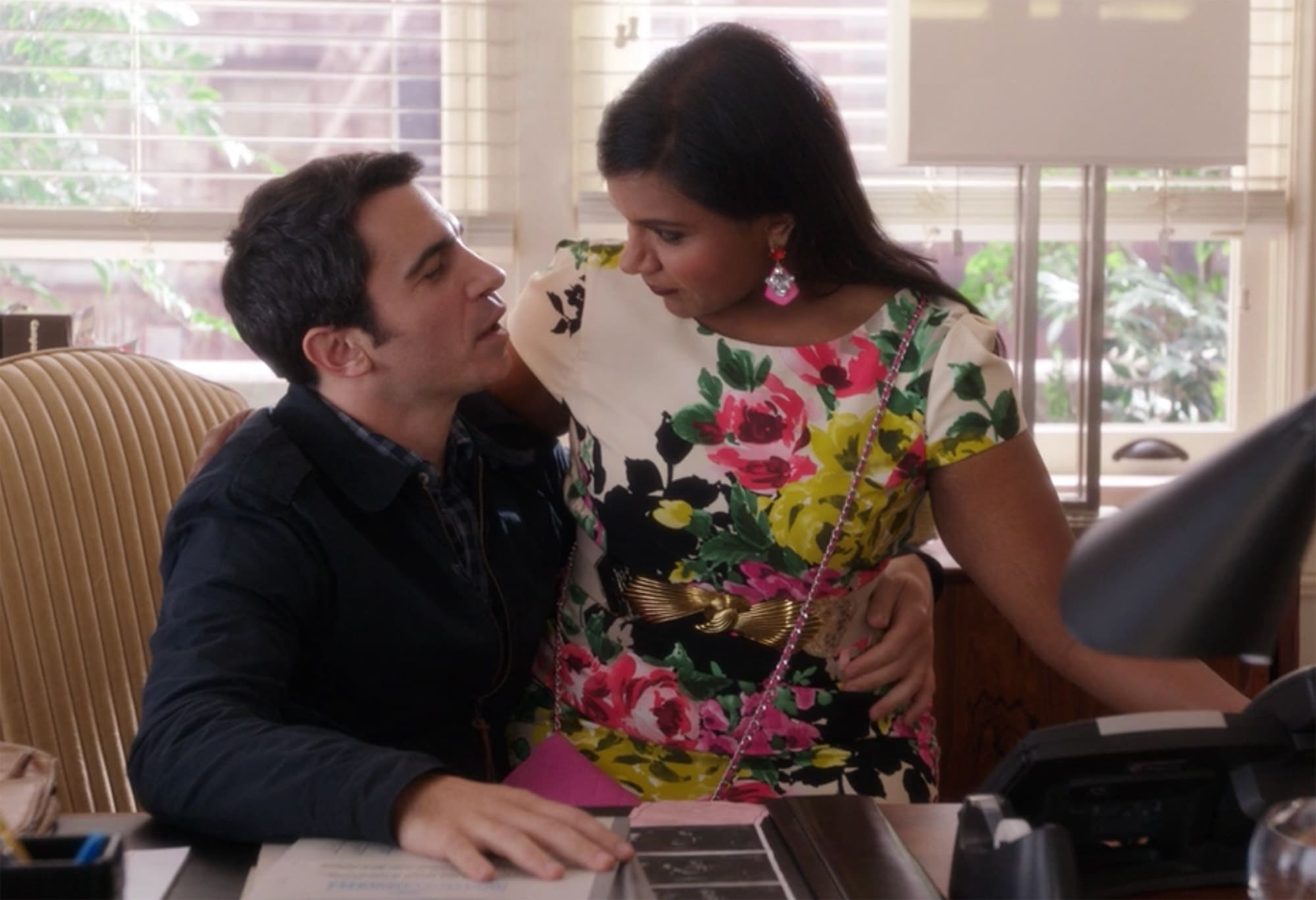 Mindy sits on Danny's lap in his office