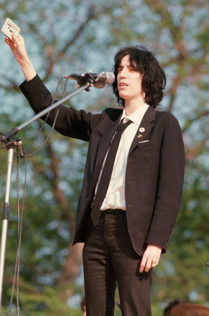 Patti de terno preto e calça jeans escura