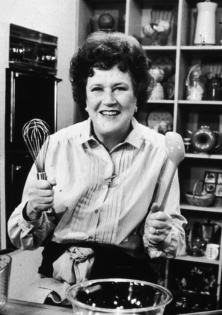 Julia Child posing with a whisk and spoon