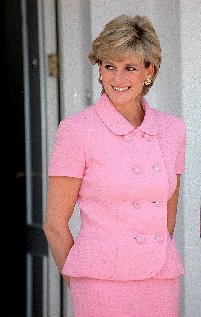 Diana usando um conjunto rosa e brincos dourados.