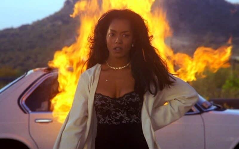 Bernie com o carro pegando fogo atrás dela