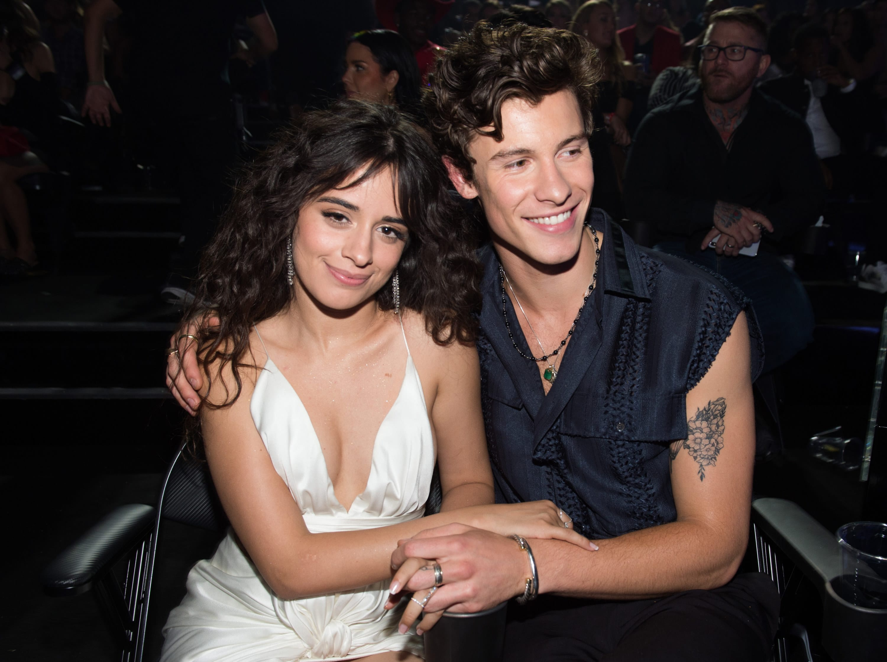 Shawn puts his arm around Camila while sitting at an event