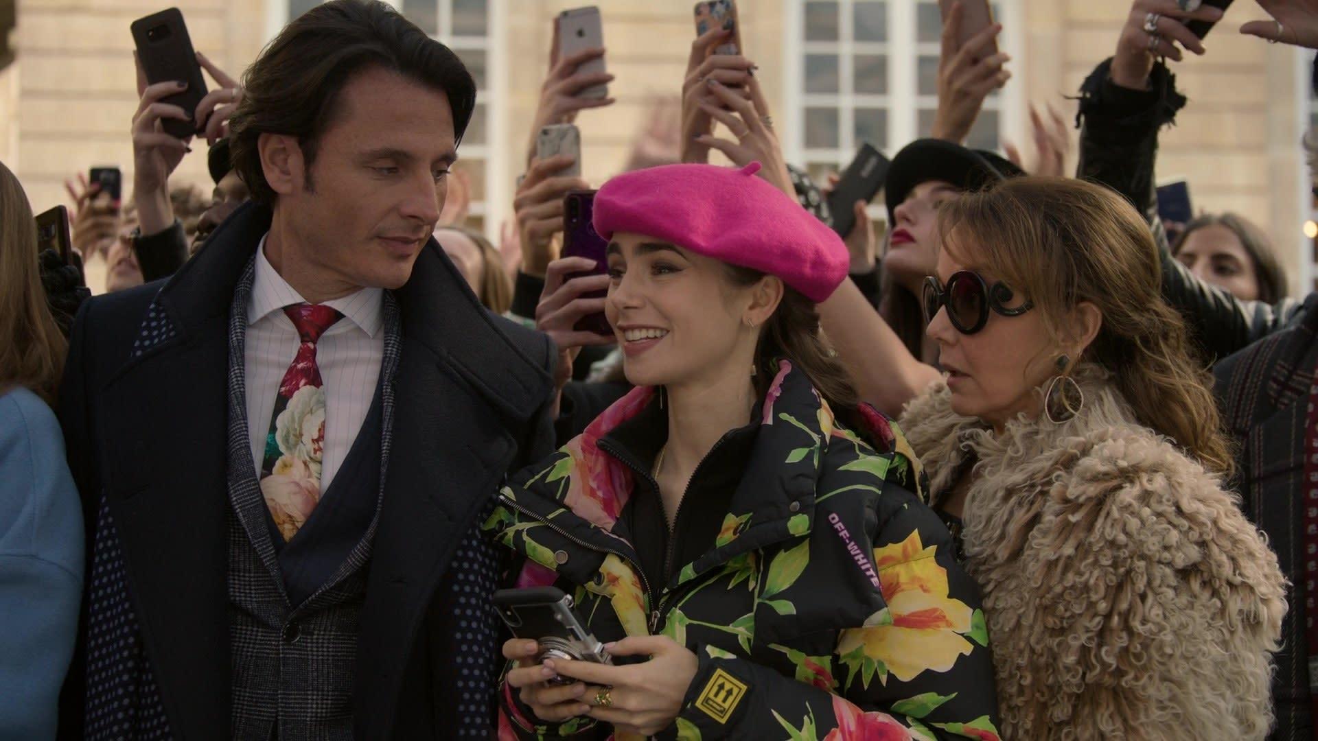 Uma mulher de boina rosa choque, casaco esportivo floral, no meio de uma multidão.