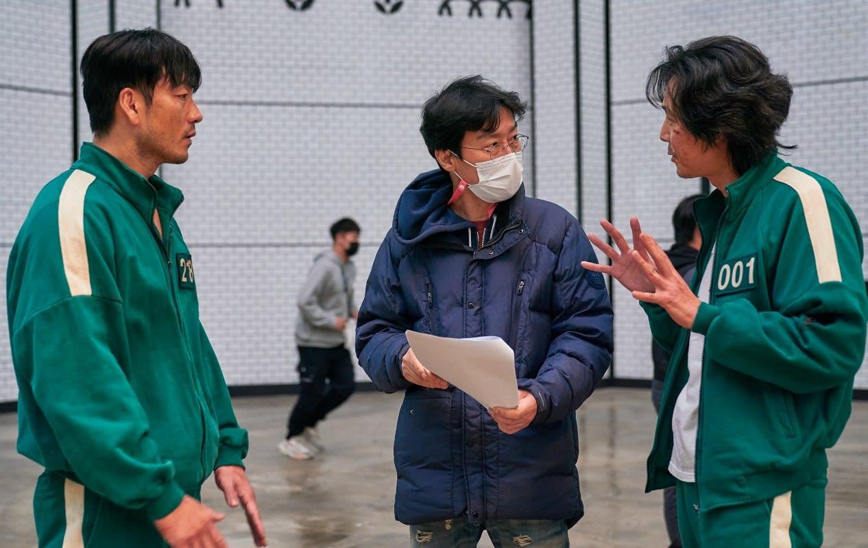 Hwang Dong-hyuk speaks to Lee Jung-jae and Park Hae-soo on set