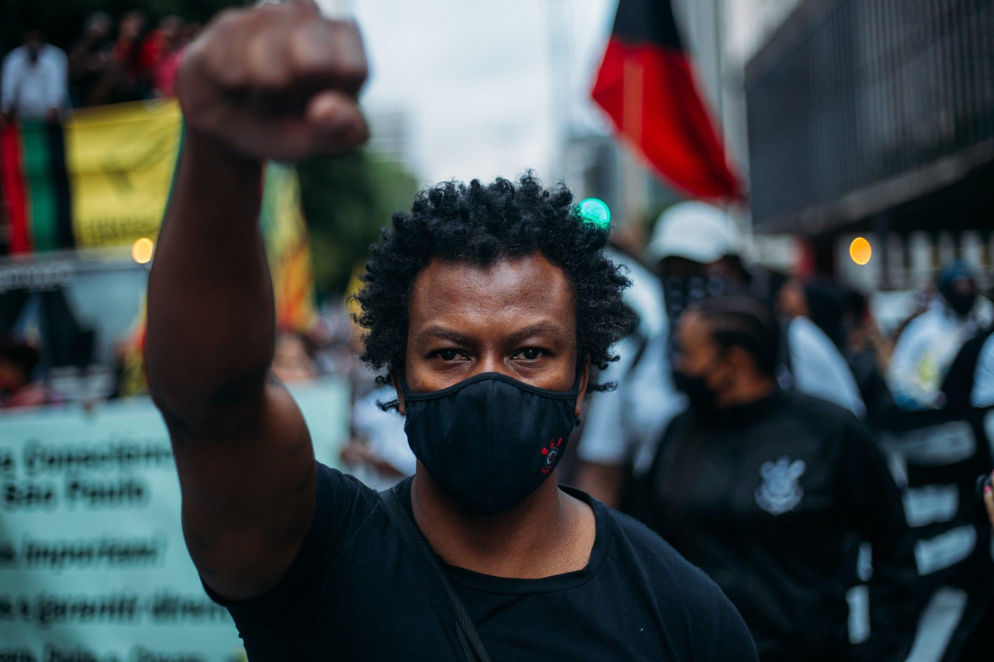 Homem negro vestindo camiseta preta encarando a câmera com punho fechado levantado no ar.