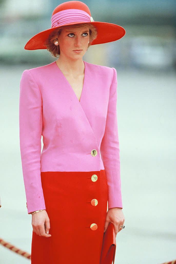 Princess Diana usando um chapéu e um vestido de mangas longas que é metade rosa e metade azul. Ela também usa joias e brincos grandes.