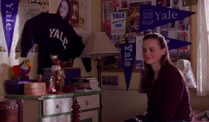 Rory sentada no quarto decorado com coisas da Universidade de Yale em Gilmore Girls