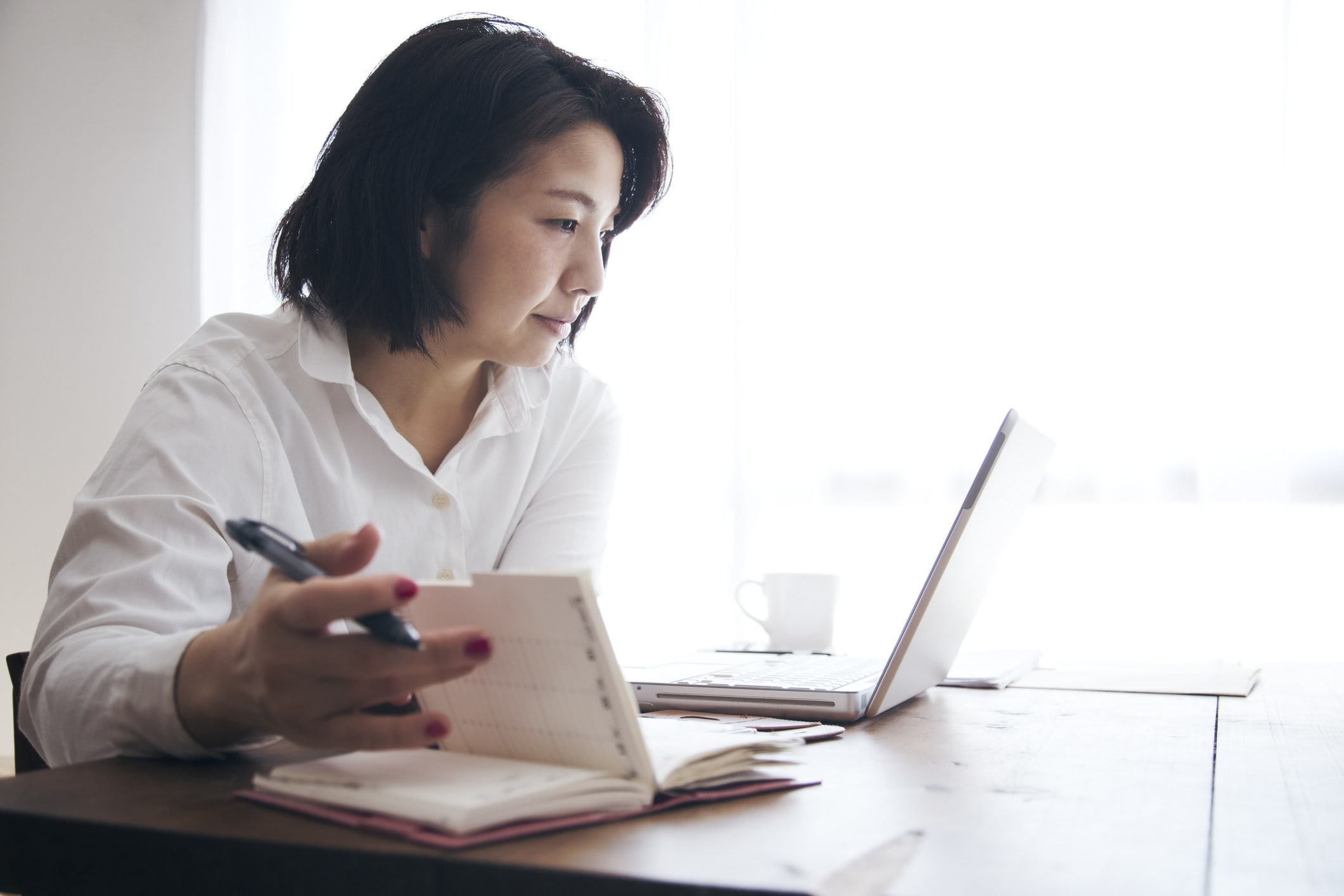 A woman writing notes while studying