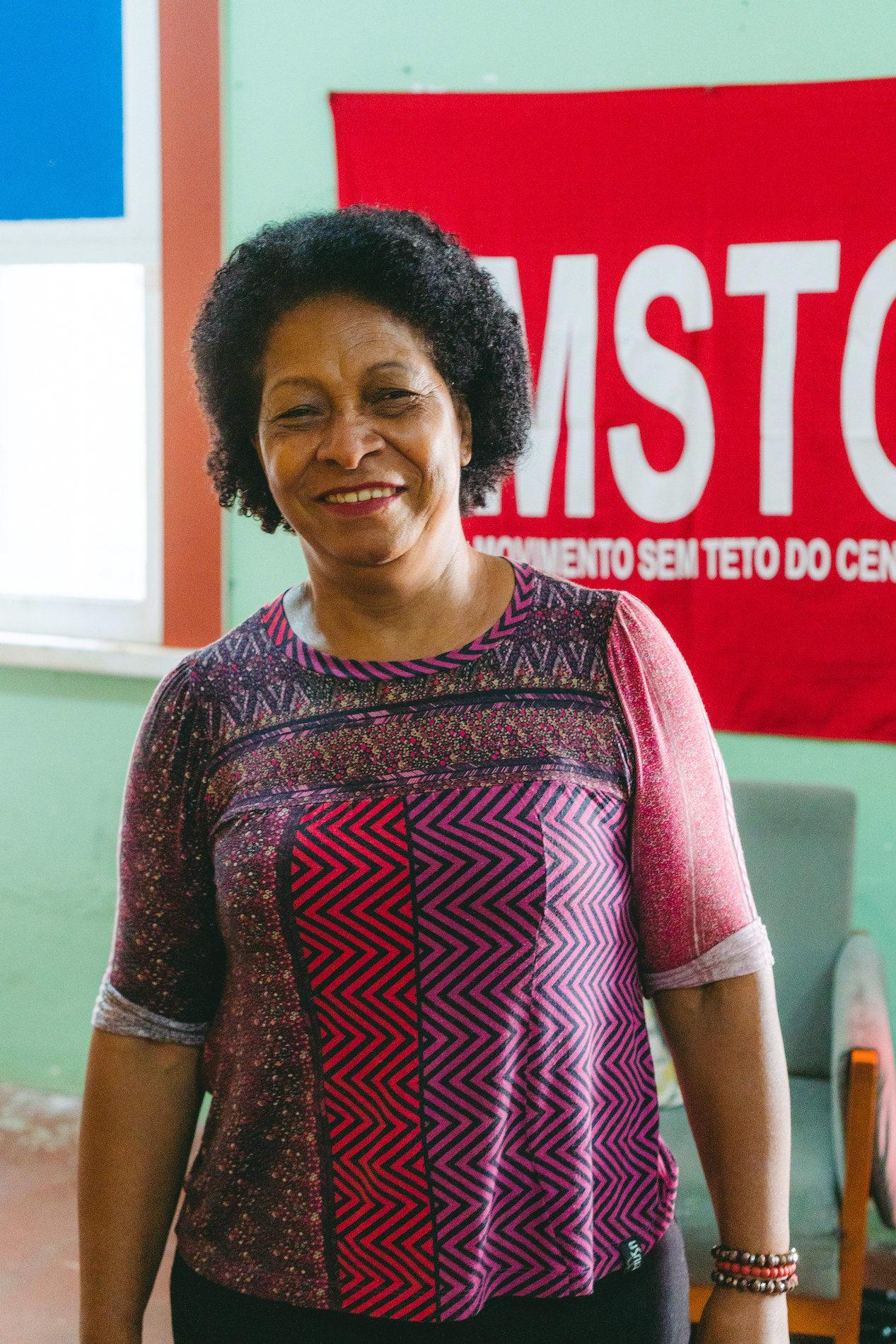 Assistente social da Ocupação 9 de Julho na frente da bandeira do Movimento dos Sem-Teto do Centro.
