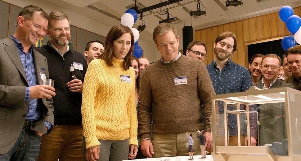 Imagem mostra vários personagens do filme reunidos em volta de uma maquete.