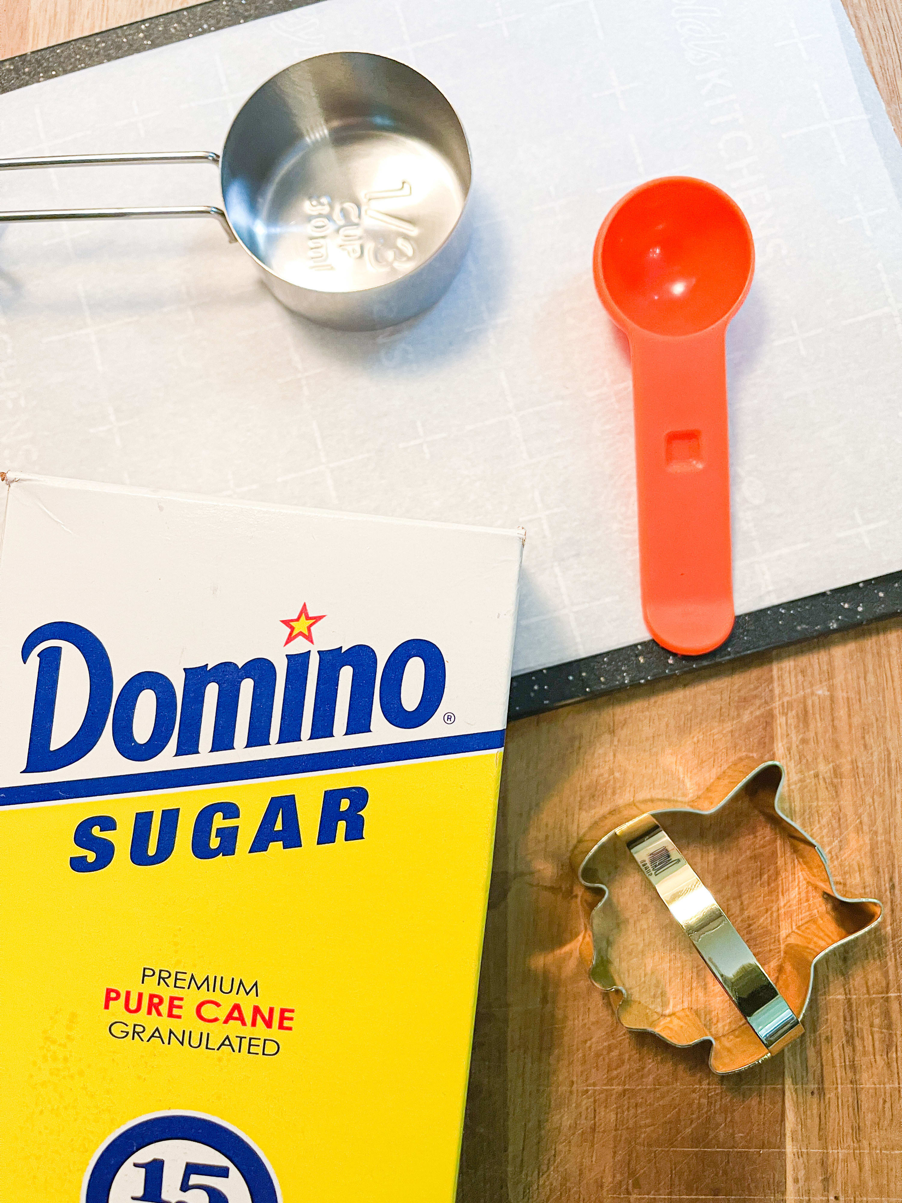 Cutting board with parchment paper, measuring cup, measuring spoon, cookie cutter, and granulated sugar