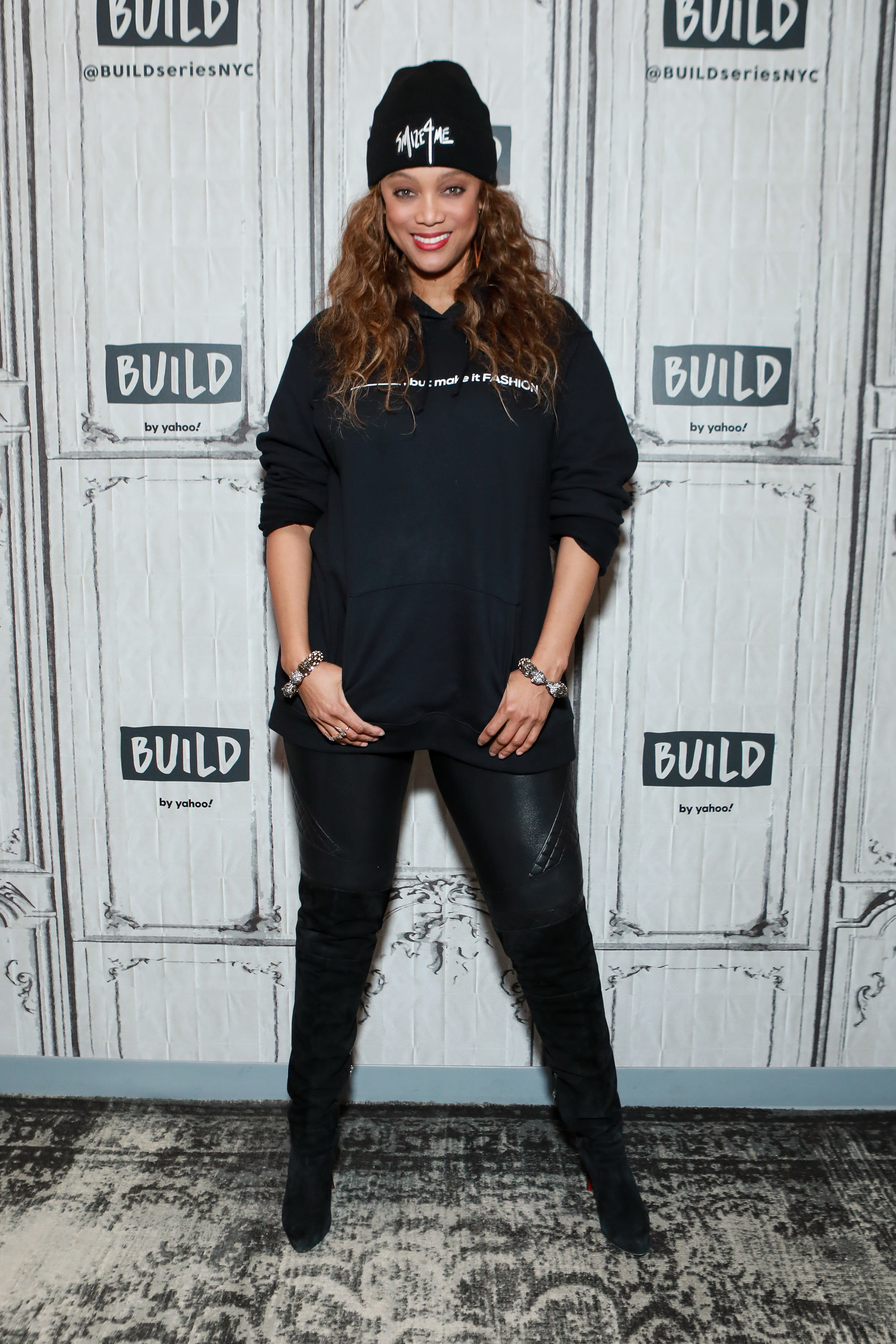 Tyra wears a beanie and oversized sweatshirt with leggings and high heeled boots.