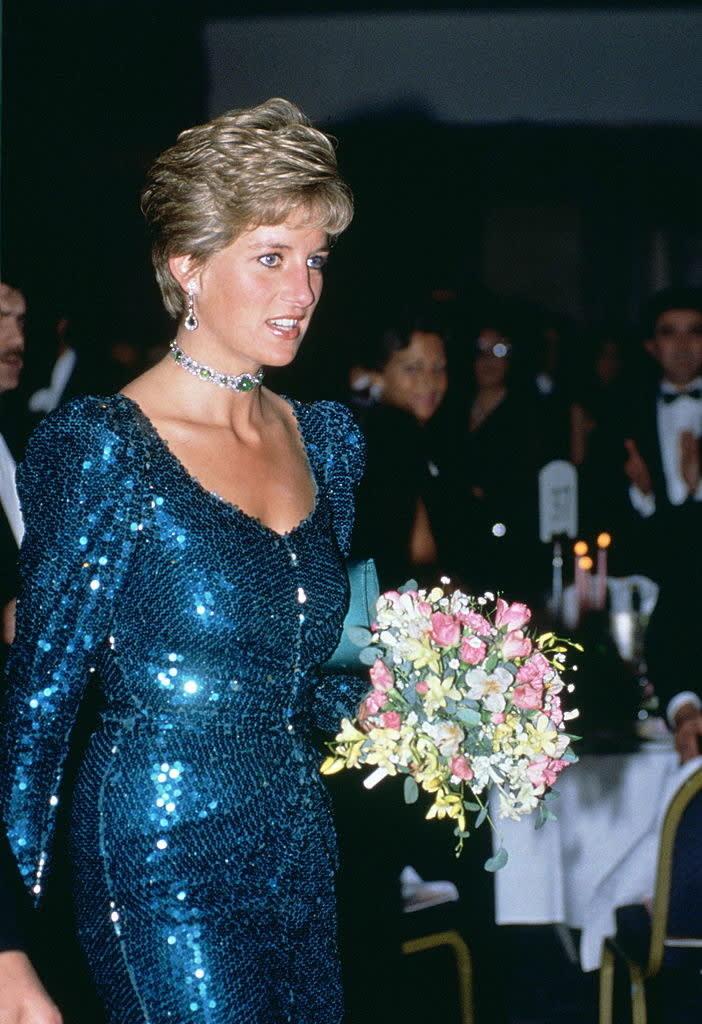 Diana usando um vestido azul de lantejoulas, ela está segurando um buquê de flores.