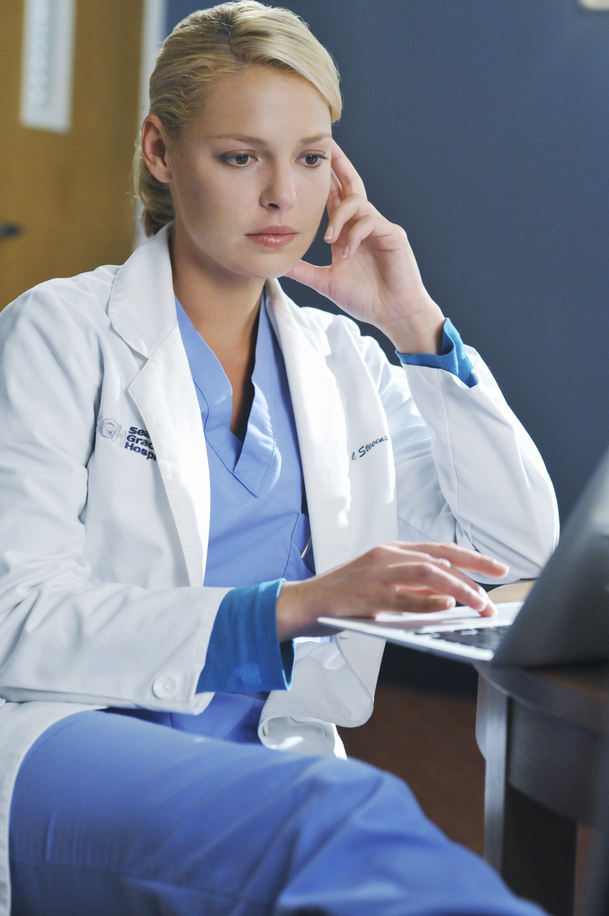 Heigl looks at a laptop with her hand touching her face while wearing scrubs