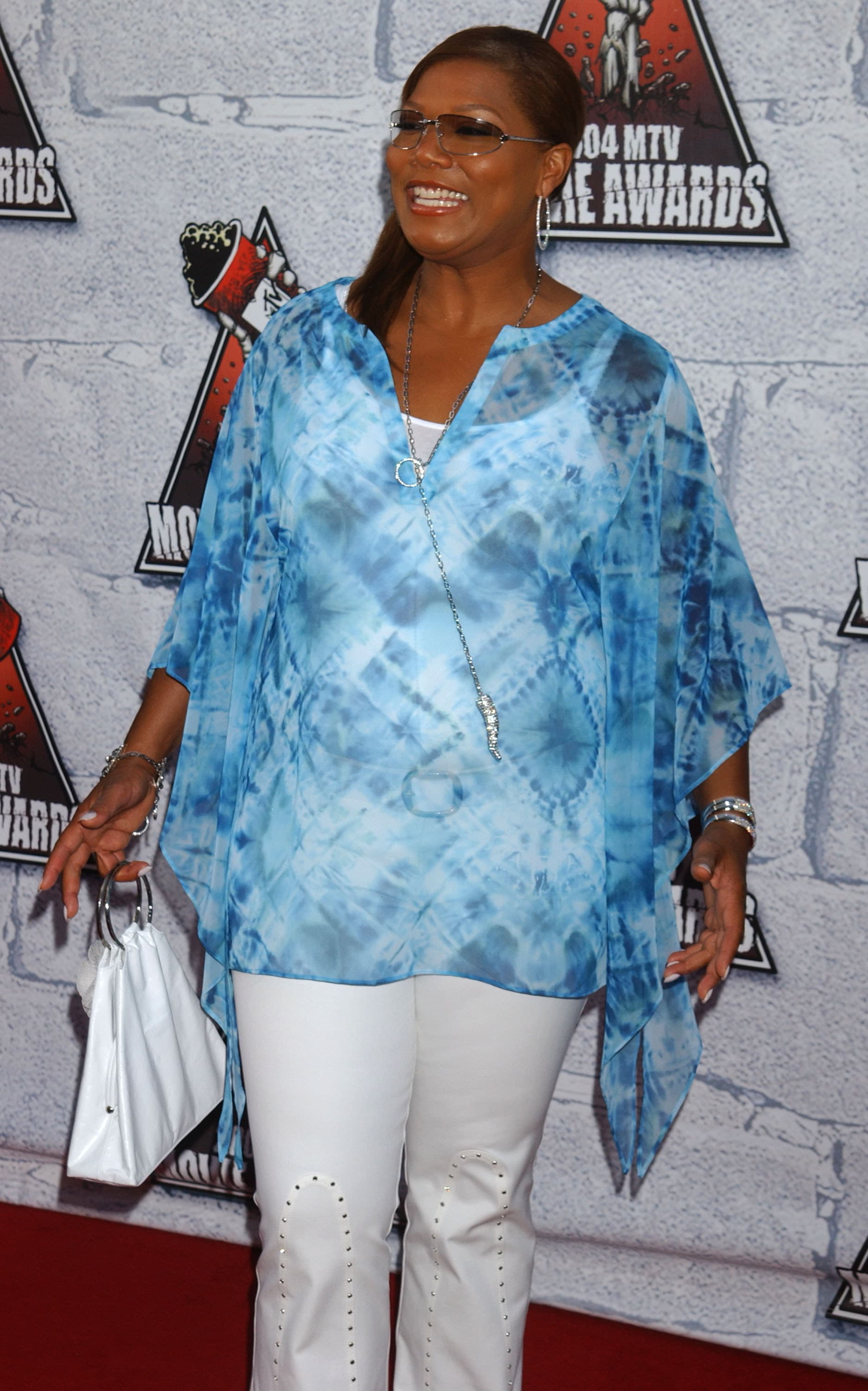 Queen wears a sheer tie-dye top over a tanktop and matching jeans with studs on the front. She also wears hoop earrings, lots of bracelets, and a triangular purse.
