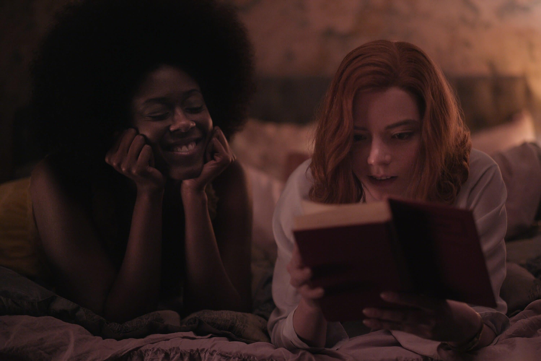 Jolene e Beth deitadas na cama vendo um livro