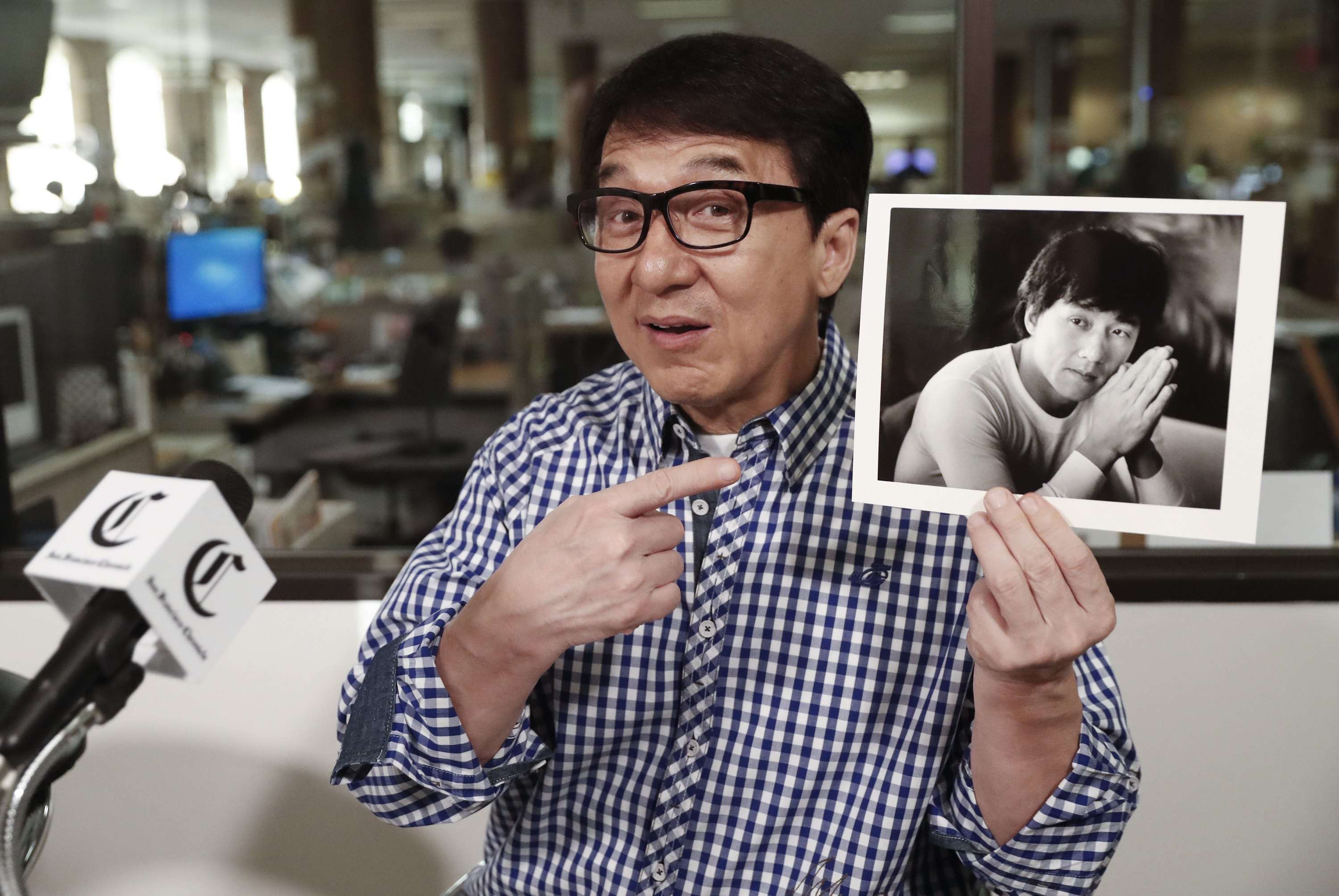 A man pointing to a picture he his holding in his other hand