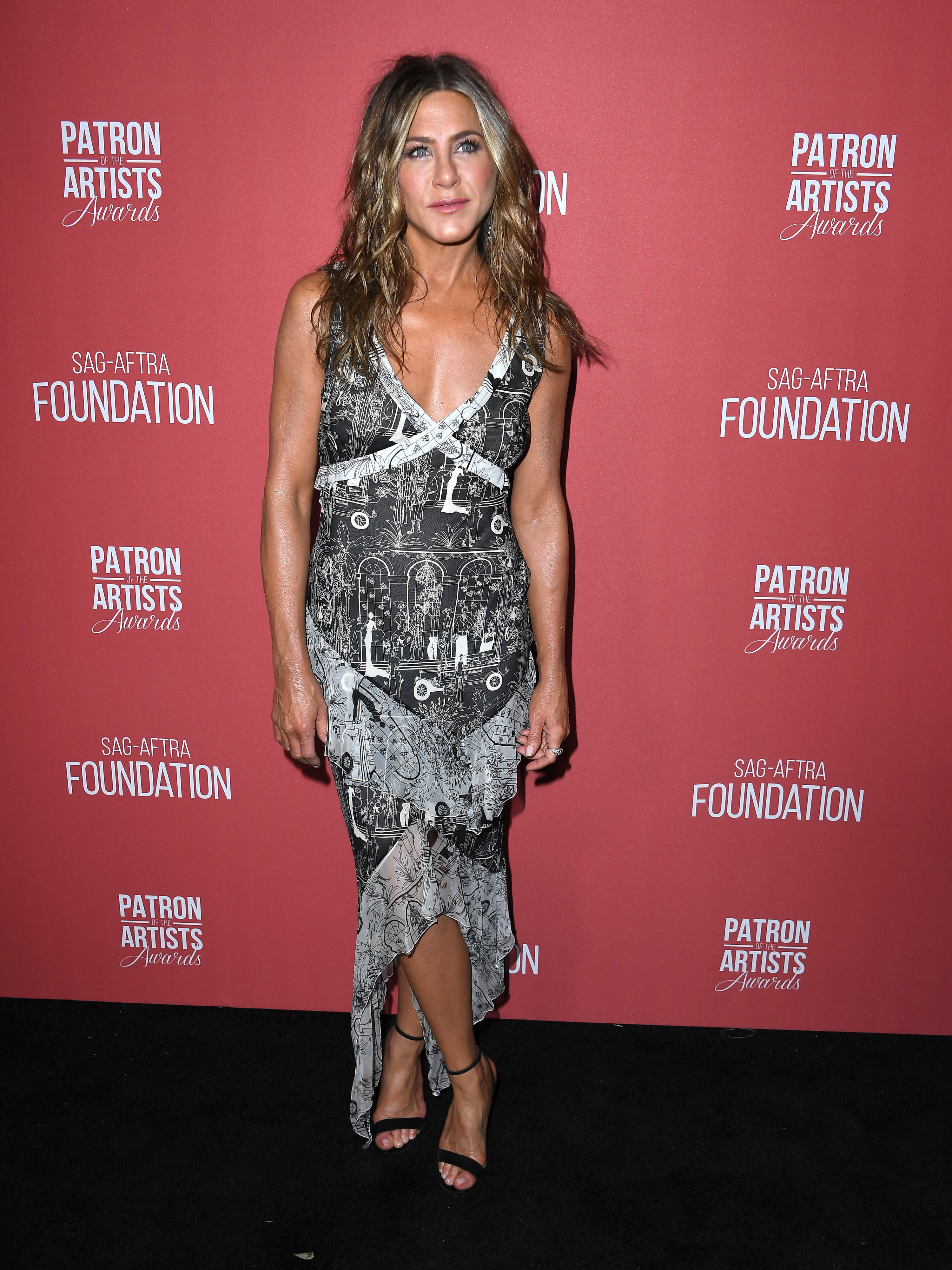 Jen wears a very busy patterned high-low v-neck dress and strappy heels.