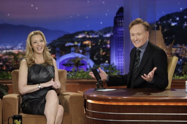 A laughing Lisa is interviewed by a smiling Conan