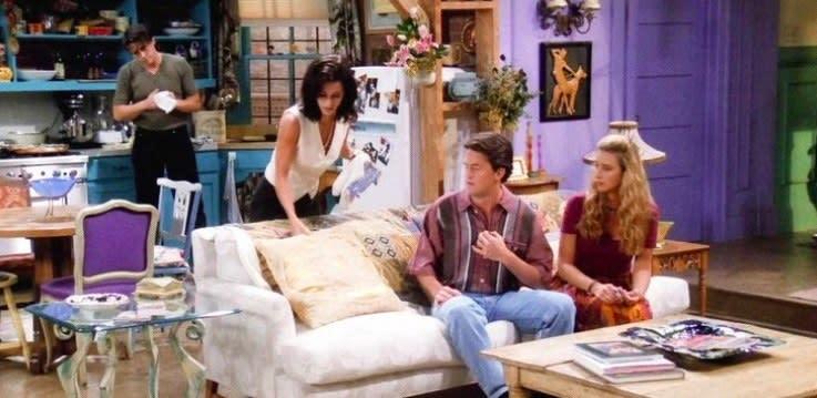 Joey e Monica na cozinha do apartamento de Monica, enquanto Chandler e Phoebe estão sentados no sofá em Friends