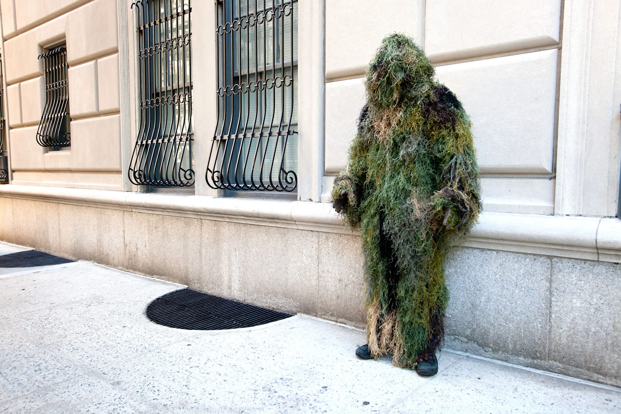 moss-covered man standing by a building