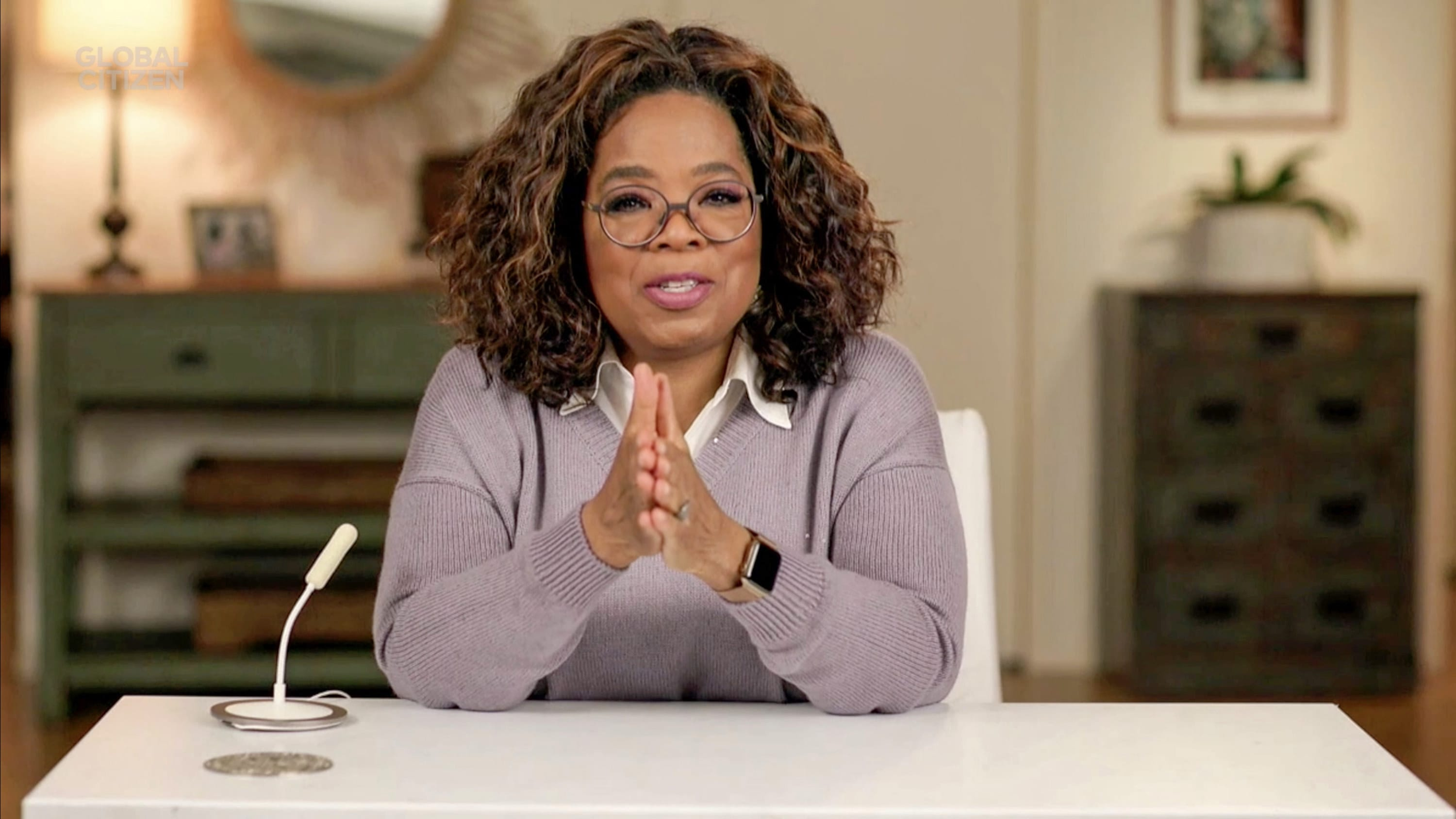 Oprah sits at a desk with her hands folded and her elbows on the desk