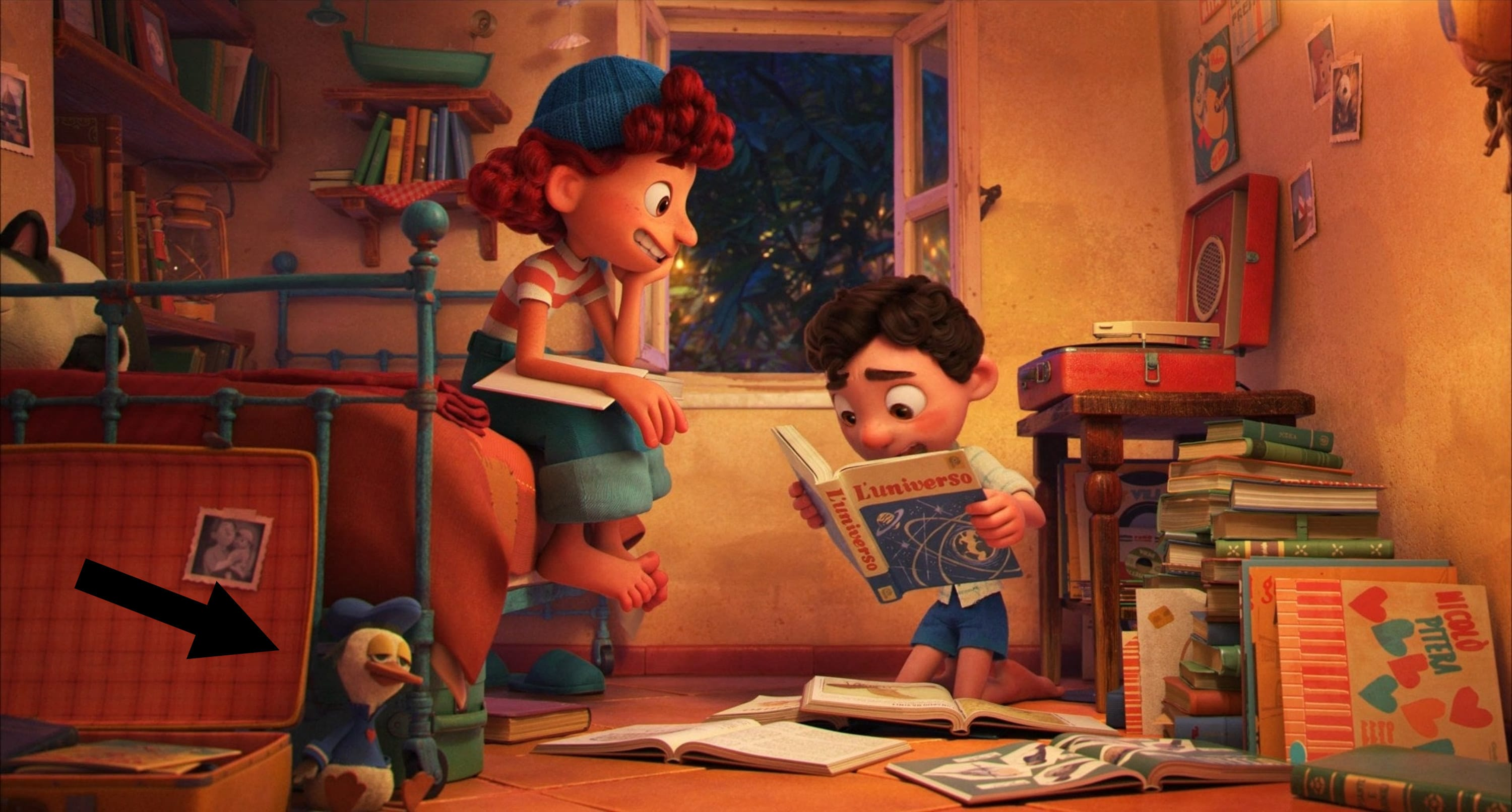 A girl and boy reading books in a room full of books and toys