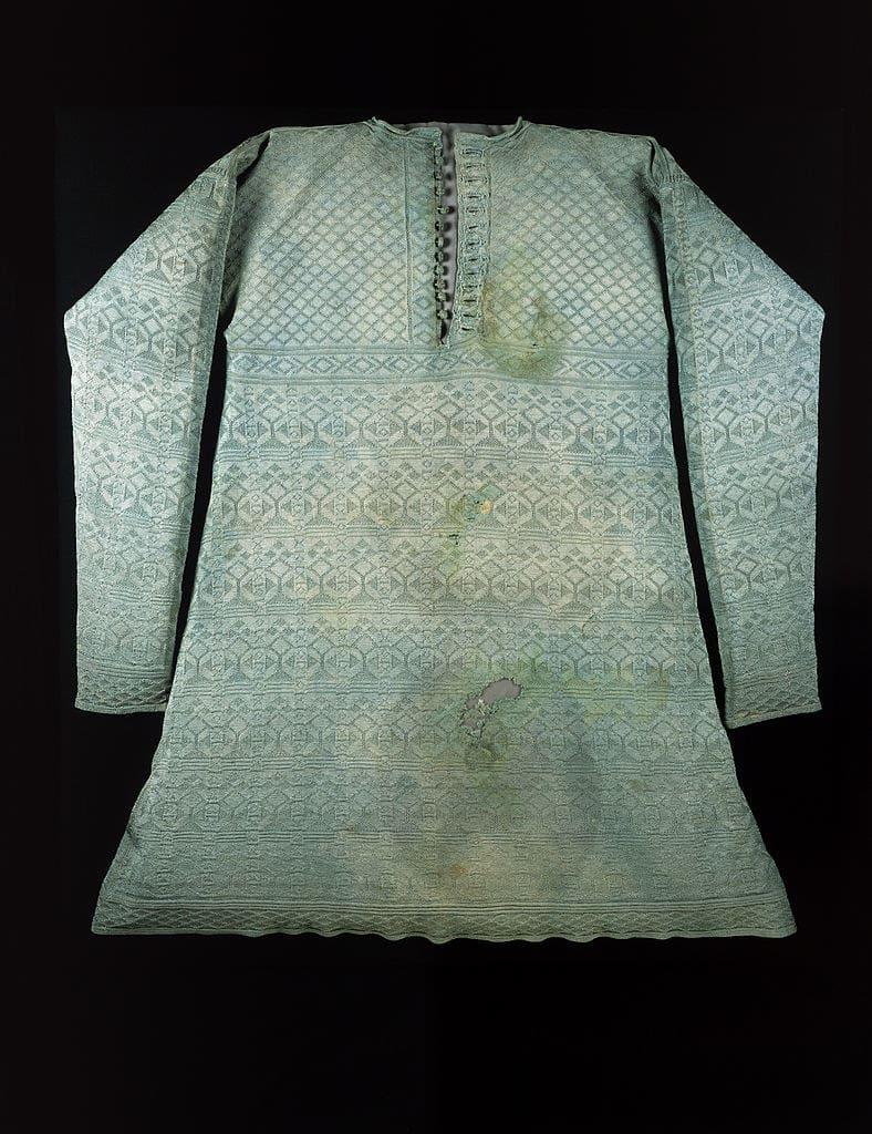 Uma camisa longa com uma estampa de padrão intrincado cheia de manchas que lembra uma túnica